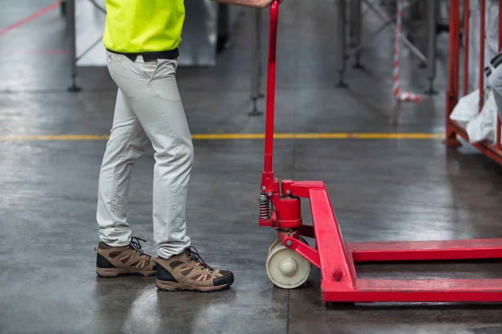 Ouvrier tirant un chariot dans une usine