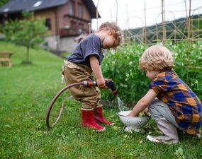 Two small children in vegetable garden, sustainable lifestyle