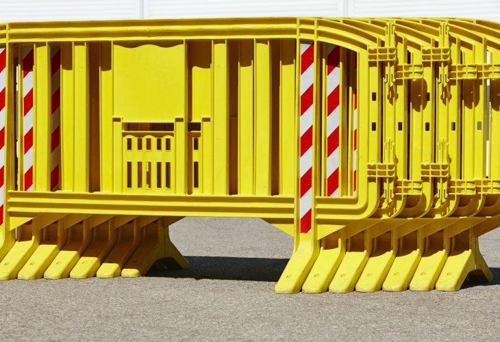 Barrière en plastique jaune au-dessus d'une route asphaltée. Sécurité
