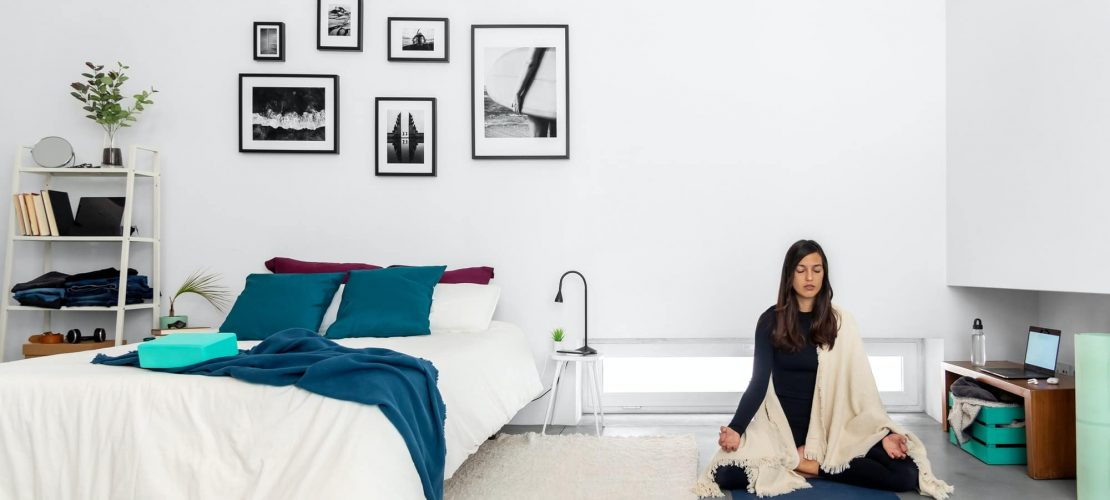 Young woman practicing yoga and meditation in lotus pose in bedroom