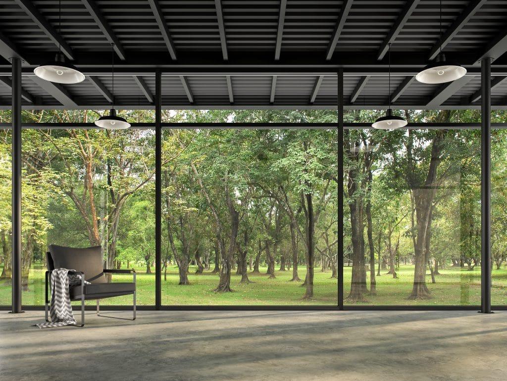 maison en verre - vue sur la foret depuis la chambre vide de style loft industriel avec vue sur le jardin, Il y a des sols en béton poli et des structures en acier noir décorées avec des chaises en tissu gris foncé avec de grandes fenêtres entourées par la nature.